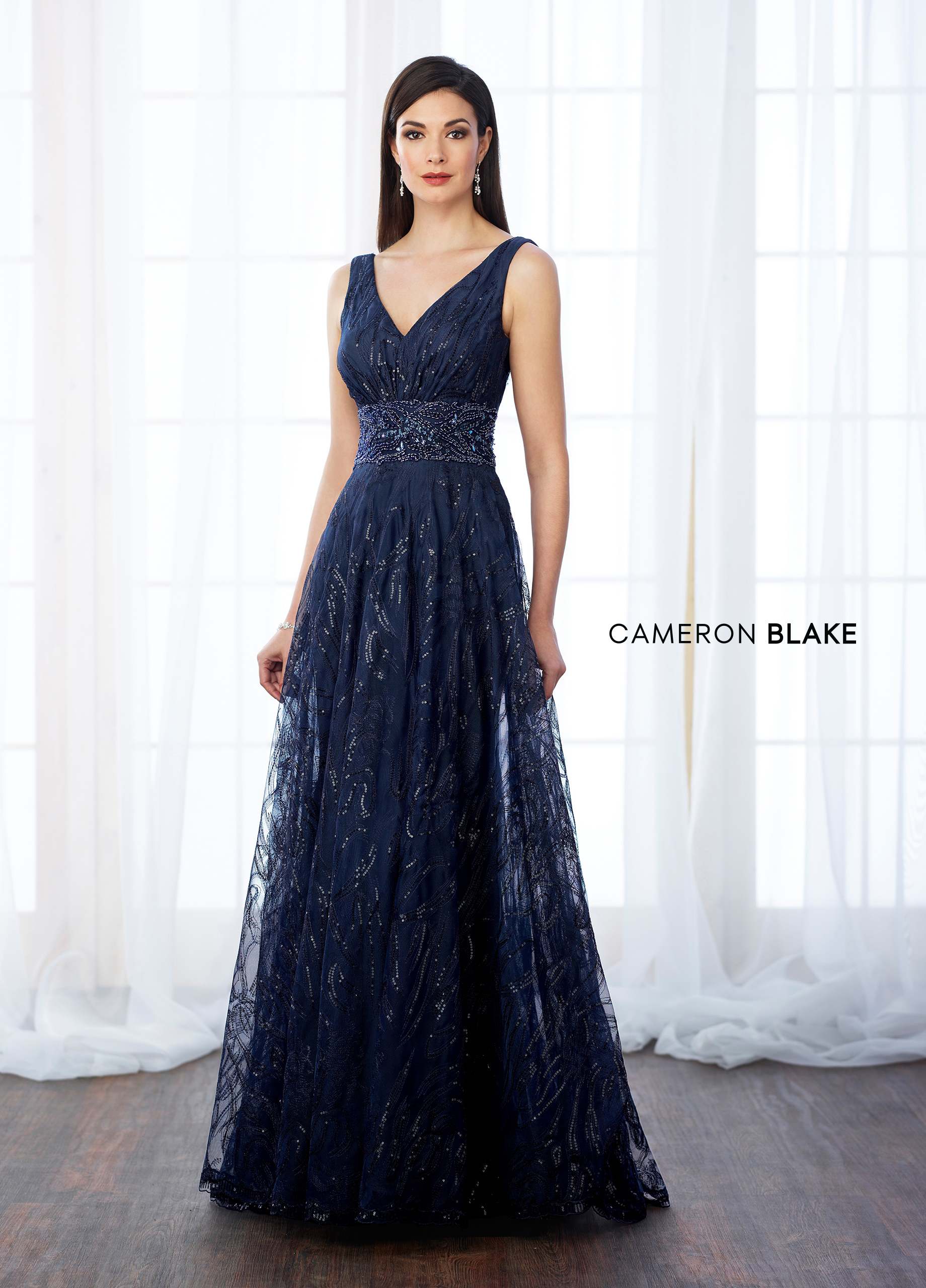 ee97353566bb Sleeveless sequin and tulle A-line gown with front and back V-necklines,  hand-beaded wide natural waistband, sweep train. Matching shawl included.