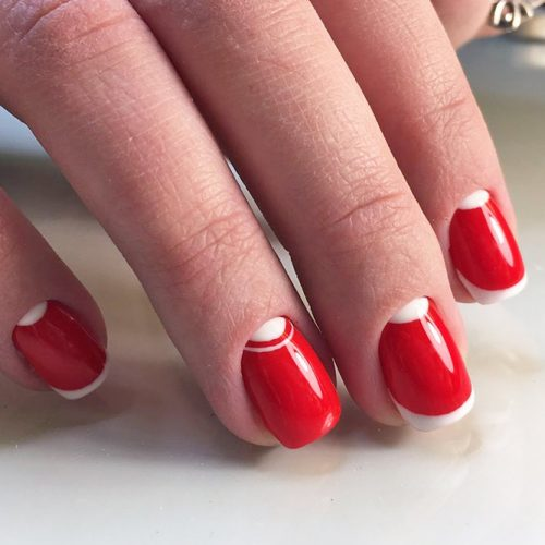 red and white nails are timeless and this modern take with short red nails with a thin white tip is super