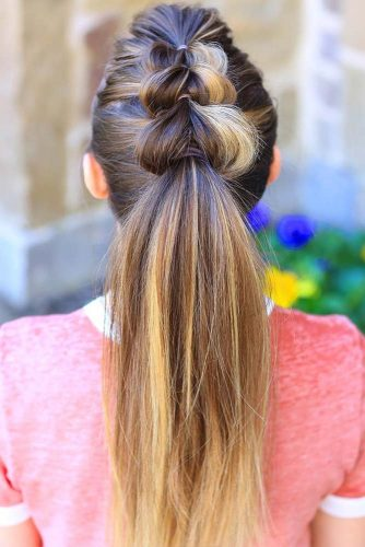 The pull-thru ponytail is not as difficult of a hairstyle as it appears. Begin by assuring that the hair is smooth and secure in a hair band.